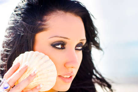 captivated: Eco Woman Of Nature Holding A Cockle Sea Shell To Her Ear Whist Listening To The Calm And Peaceful Ocean Breeze During A Beachfront Vacation