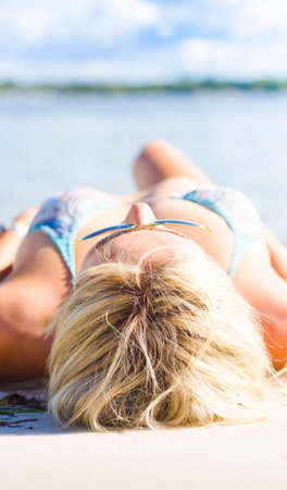 soporific: Focus On The Head Of A Blonde Girl Asleep On The Sand At A Beach Location During A Tourism Vacation In A Depiction Of Peace Quiet Stillness And Silence