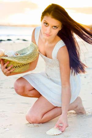 mujer arrodillada: Señora Hermosa Joven Recogida de Seashells por la orilla Durante Sundown O Anochecer En una imagen que representa la armonía pureza y bienestar