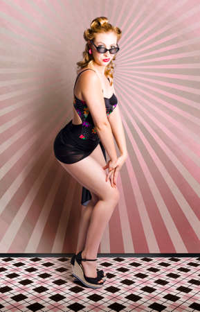 Vintage Style Retro Portrait Of A Sexy PinUp Girl Posing In Sixties Era Swimwear On Pink Striped Background