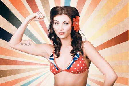 tough girl: Vintage photo of beautiful pinup girl with american star tattoo showing the power of womens rights when flexing muscles in retro fashion style