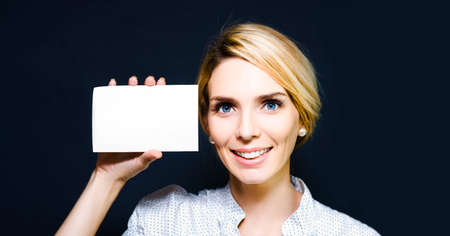 credentials: Young woman holding up a blank business or trade card to establish her credentials, qualifications and identity