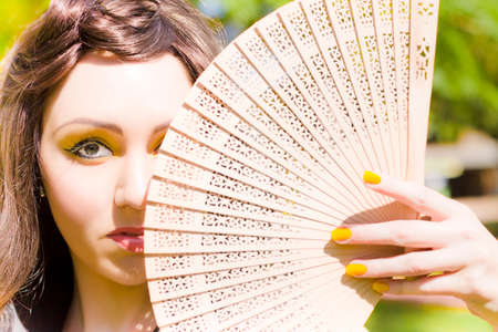 timid: Shy Timid And Withdrawn Woman Glances With One Eye Out Over A Wooden Asian Fan While Hiding Away In The Great Outdoors In A Nervous And Anxious Photograph