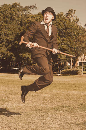 midair: Sepia View Of A Happy Young Man With Retro Suit, Bowler Hat And Walking Stick Jumping Midair On Grass