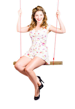 fifties: Isolated portrait of a beautiful fifties pin up girl playing on makeshift swing on white background Stock Photo