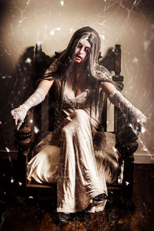 haunting: Haunting horror scene with a strange scary vampire girl with blood stained mouth sitting in an old dusty house filled with cobwebs. Story of pain and suffering