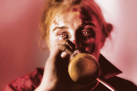 grisly: Creepy portrait of a drunken female ghoul drinking beer at Halloween party event Stock Photo