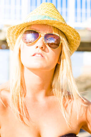 holidaying: Peaceful And Relaxed Daydreaming Female Tourist Watching The Sunset In A Dream Vacation Or Holiday Concept Wearing Reflective Sunglasses And Straw Hat Stock Photo