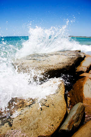 impacted: Waves Rock A Beach Shoreline In Splashes Of A Coastal Collision Stock Photo