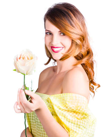 tender sentiment: Smiling young woman in dress with blooming rose, white background. love blooms