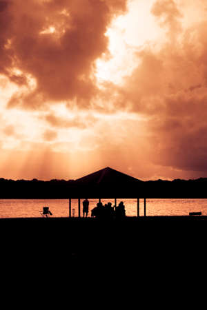 beaming: A Family Seated At A Park Picnic Table Silhouetted In Front Of Beaming Rays Of Afternoon Sunlight Piercing Tempest Clouds