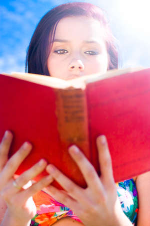absorbed: Close-up On The Face Of An Absorbed Woman Reading A Red Book Against A Blue Sky In A Serene Quiet And Tranquil Summer Recreational Hobby