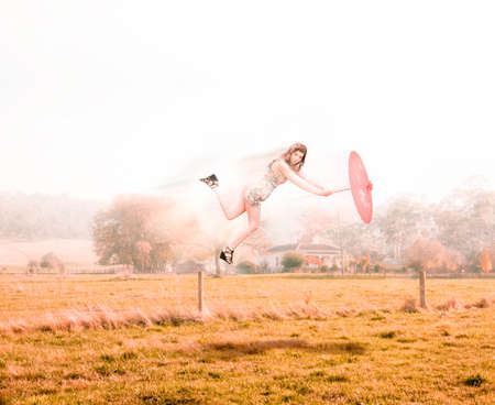 50s fashion: Creative Image Of A Vintage Woman In Stylish 50s Fashion Clothing Holding Retro Umbrella Being Blown Away Over A Rural Country Field In A Fashion Storm