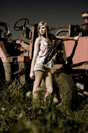 farmyard: A Lady Rest Up On Vintage Farmyard Machinery As She Watches The Sun Set While On The Farm At Dusk Stock Photo