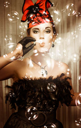 haute couture: Beautiful party girl in haute couture and a fascinator hat blowing a myriad of iridescent bubbles during a birthday celebration
