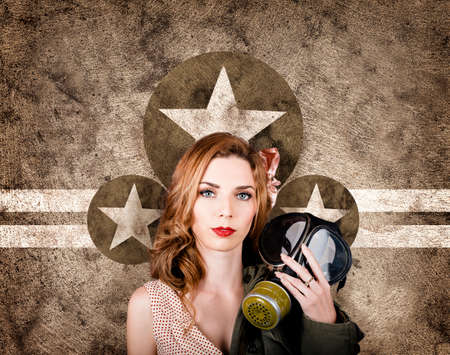 sombre: Vintage WW2 portrait of a sombre 1950s pinup woman holding army gas mask when stopping to pay tribute to the fallen. Memorial day concept