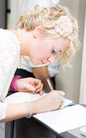 wedding guest: Woman Wedding Guest Signs The Attendance Register Book - Guestbook During A Formal Wedding Celebration