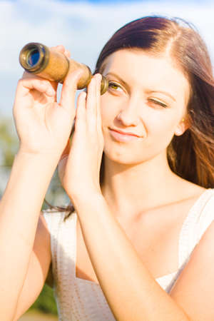 olden day: Pretty Woman Gazing And Staring Into The Distant Horizon Though An Antique And Bygone Telescope In An Old Fashioned Conceptual Stock Photo