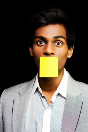 notelet: Talkative forgetful office worker silenced by his colleagues by having a blank sticky memo plastered over his mouth on which to write a reminder or schedule