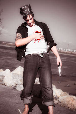 bloodied: Bewildered And Bloodied Pirate Looks Down At Bullet Hole Wound In His Chest During A Beachfront Gun Battle Stock Photo