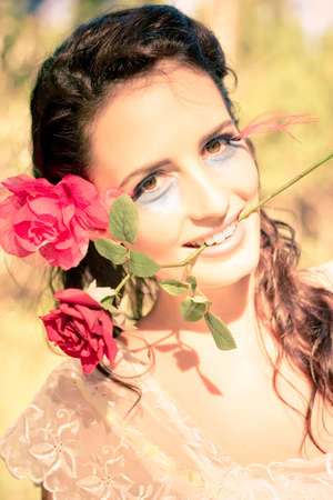 beautiful rose: Love Is In The Air Shown By The Smile Of A Attractive Woman Blossoming An Expression Of Delight While Holding A Floral Red Rose In A Happy In Love Concept