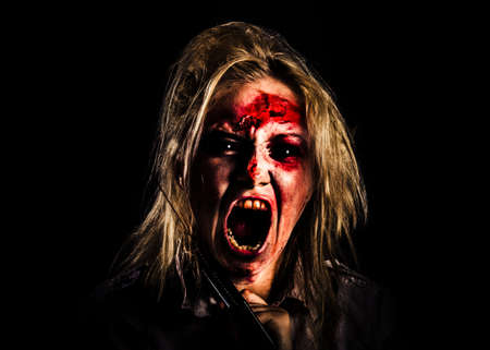Face of an evil zombie girl screaming out in bloody horror while holding a hand saw on black background