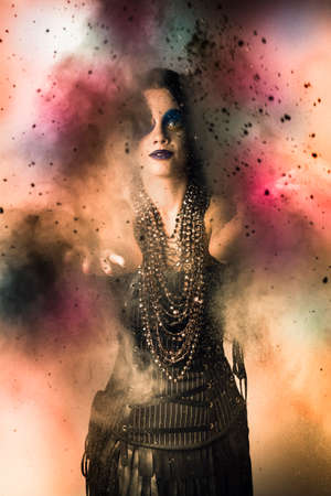 spellbinding: Magical female jester bedecked in jewellery casting a medieval spell while throwing a cloud of colourful magic powder to invoke netherworld spirits in a mystical ritual Stock Photo