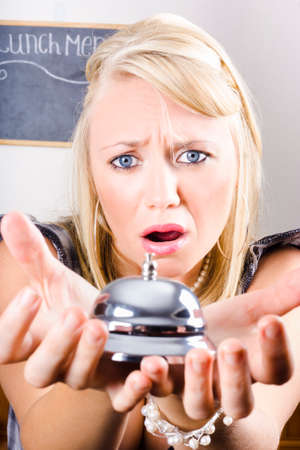 dismayed: Upset And Unhappy Female Patron Holding Silver Service Bell In Disgust When Receiving Bad Customer Service Stock Photo