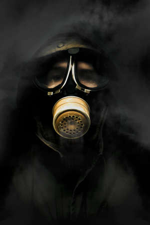 wearer: Soldier Standing In The Dead Of Night Breathing Through A Military Issued Gasmask While A Haze Of Toxic Gas And Smoke Circulate Around The Air Stock Photo