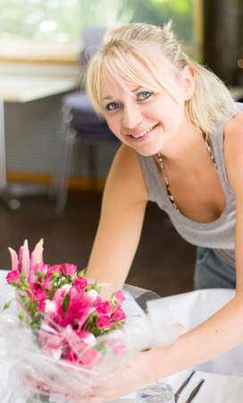 wedding table decor: Smiling Wedding Planner Setting Up The Wedding Reception Venue By Organizing The Table Flowers Decorations Before The Formal Function Begins Stock Photo