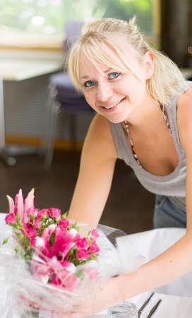 matrimonio feliz: Sonriendo planificador de la boda Configuración de lugar de la recepción de la boda por la organización de la mesa Flores Decoraciones antes de la función formal comienza