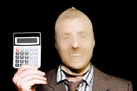 Laughing male robber wearing a stocking mask holding up a portable mathematical calculator in a Cost of Crime concept isolated on black background Stock Photo