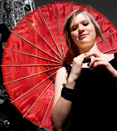 fair complexion: Smiling Happy Woman Holds A Bright Red Parasol At A Carnival Stock Photo