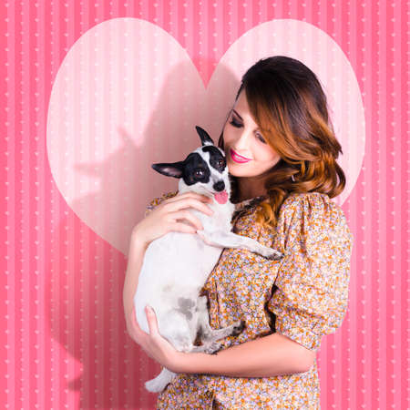 fox terrier puppy: Beautiful Woman Cuddling Her Small Mini Foxi Dog Inside. Conceptual Of Pet Love On Pink Heart Background Stock Photo
