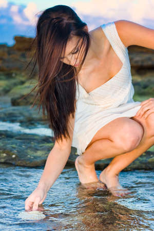 sea shell: Beauty In Nature Concept Sees An Attractive Young Brunette Woman Picking Up A Sea Shell From Shallow Sea Water In A Rock Pool Stock Photo