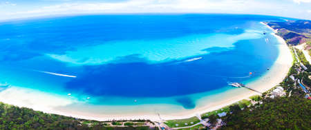 An aerial view of the beautiful crescent shaped bay and clear blue waters of Moreton Island, Australia
