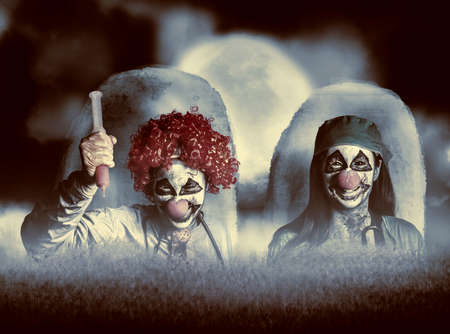 rising dead: Scary combined photo illustration of 2 evil zombie clown doctors rising from the dead at a spooky cemetery amongst a set of headstones during a full moon night of terror