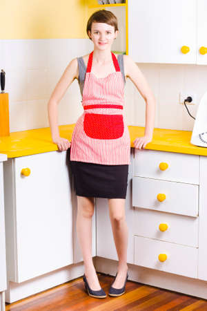 pinafore: Pretty young woman wearing red pinafore with stripes over a gray dress in a modern kitchen with yellow work tops and white cupboards