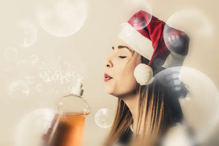 grime: Creative vintage portrait of a beautiful blond housewife blowing away dirt and grime when preparing for the holiday season. Christmas cleaning Stock Photo