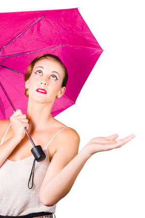 inclement: Attractive young woman sheltering under pink umbrella, white background with copy space Stock Photo
