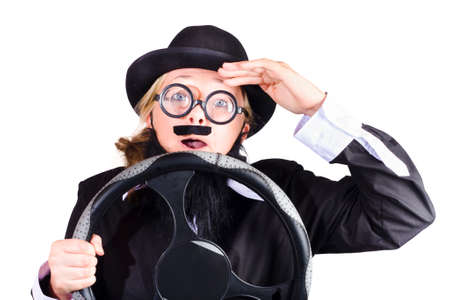 near sighted: A woman in mens clothing and moustache behind a steering wheel, driving like a near-sighted old man