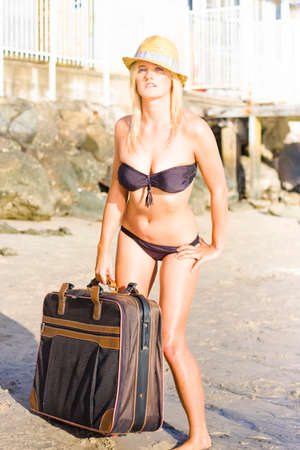 longing: Blonde Female Wearing Bikini And Sunhat And Expression Of Longing Standing Next To Brown Luggage As If Her Greatest Desire Is To Be At The Beach