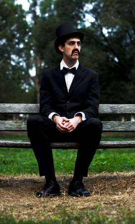 melancholy: Tired Melancholy Man Wearing Top Hat Sits Depressed On A Park Bench Grieving After A Funeral Remembrance Service