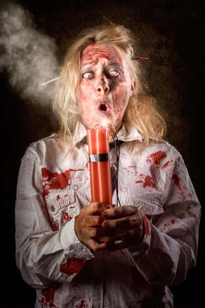 timebomb: Funny portrait of a young monster woman with scared crazy expression holding bomb with lit fuse on dark grunge background. Halloween countdown Stock Photo