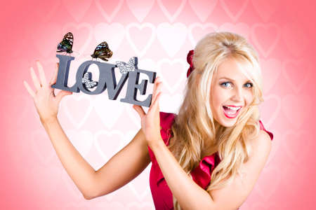girl holding sign: Lovable blond girl holding sign inscribed with the words love in a touching display of affection