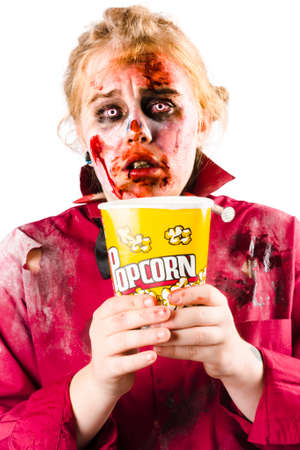 horrific: A woman in zombie makeup and outfit watching a scary movie with a bucket of popcorn. Stock Photo