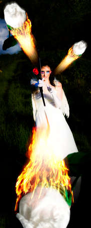 angel roses: Artistic And Creative Portrait Of Cupid The Angel Of Love Shooting White Roses With A Bow And Arrow To Set The Flame Of Her Desire On Fire Stock Photo