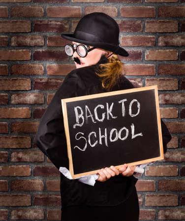 director de escuela: Detrás de un director de mirada divertida celebración de tablero negro con de nuevo a la escuela por escrito con tiza. Escuela de fondo de la pared de ladrillo