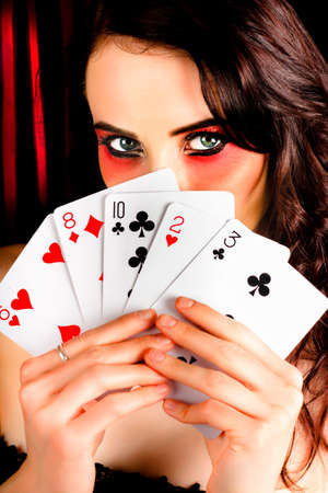 surreptitious: Beautiful female poker playing with elegant makeup holding a hand of playing cards inside casino