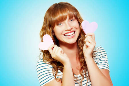 aloft: Mischievous smiling valentine girl holding aloft two pink hearts on either side of her face on a turquoise blue background with colour gradient Stock Photo